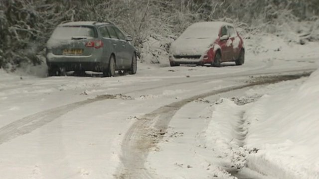 Snow covered cars on road