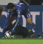 Chelsea's Eden Hazard retrieves the ball over the prone figure of the ball boy
