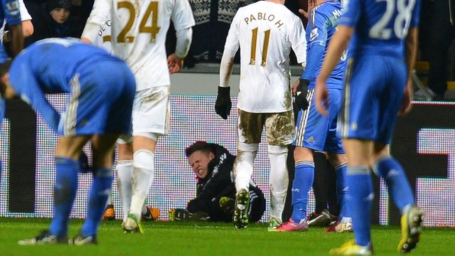 A ballboy lies on the ground after a altercation with Chelsea&#039;s Eden Hazard 