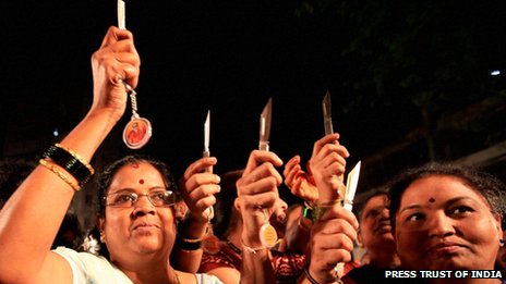 Group of women holding up their knives given by the Shiv Sena