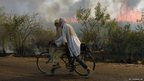 Cyclists pass a burning sugar cane field.