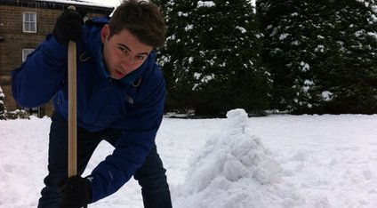 Ricky making a pile of snow.