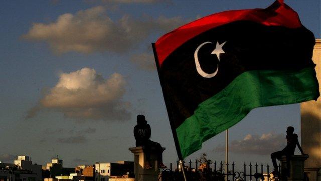 Libyan flag over Benghazi skyline