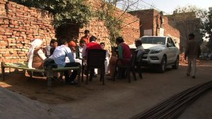 Farmers in a rural area in India sitting in front of a luxury car