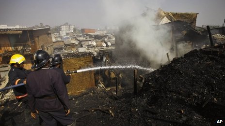 Firefighters try to douse a fire in a shanty in Mumbai on Friday, Jan 25, 2013