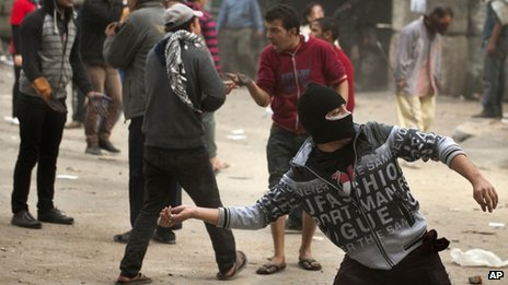 An Egyptian protester throws a stone at police in Tahrir Square in Cairo 