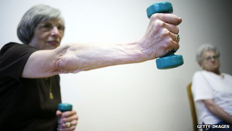 An elderly lady takes part in a fitness class