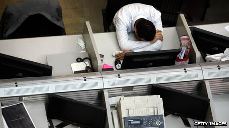 A man slumps at his desk