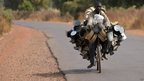 A man cycling with a loaded bicycle near Segou in Mali - Tuesday 22 January 2013