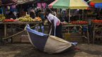 A vendor at Gudele market in Juba, South Sudan, picking up a large umbrella - Wednesday 23 January 2013