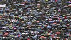 Mourners with umbrellas at John Nkomo's funeral in Harare, Zimbabwe - Monday 21 January 2013