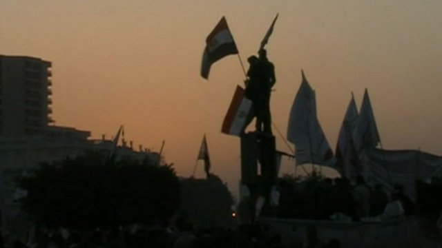Silhouettes of protesters with flags in Tahrir Square