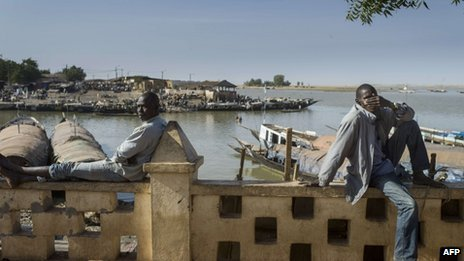 Malians sit on a wall along the Niger River in Mopti, 23 January 2013