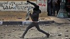 Egyptian protesters throw stones during clashes near Tahrir Square, Cairo, 25 January