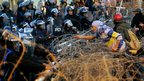 Protesters tug at razor wire protecting presidential palace in Cairo. 25 Jan 2013