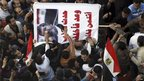 Protesters in Cairo hit a poster of President Mohammed Morsi, 25 January 2013