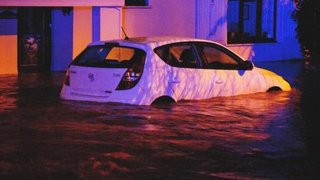 A car is surrounded by flooding in Llanddowror