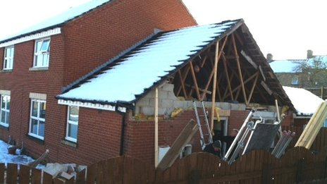 House with roof exposed after gable end collapsed