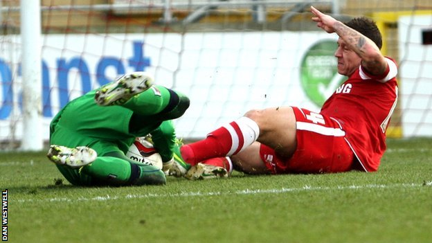 Leyton Orient's Charlie MacDonald slides in on Notts County goalkeeper Bartosz Bialkowski