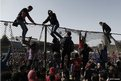 Al-Ahly fans climb over a fence at their Cairo home stadium as they celebrate the death sentences passed on 21 fans of Port Said's al-Masry football club involved in a football stadium massacre last year on 26 January 2013
