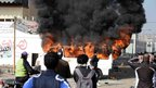 A minibus is set on fire by protesters outside the Port Said prison on 26 January 2013
