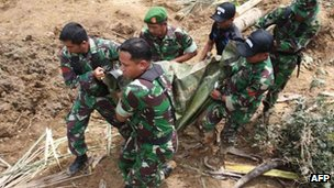 Indonesian soldiers evacuate a dead body, the victim of a recent landslide that hit Nagari Sungai Batang village in Agam