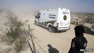 A car belonging to the forensic medical services heads towards a well where bodies were found on Monday