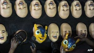 "Employees work on masks of Brazilian football star Neymar, the president of the Brazilian Supreme Court Joaquim Barbosa and the mascot of the Brazil 2014 Fifa World Cup, ""Tatu Bola-Fuleco"""