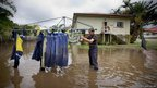 Tony Hall stands in floodwaters as he checks his washing on a clothes line in the inner Brisbane suburb of Newmarket