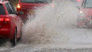 Cars drive through flood water