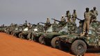 Chadian soldiers stand in front of their armoured vehicles as they prepare to leave Niger for Maqli, on 24 January.