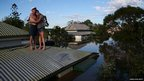 Two people embrace on their roof above a flood