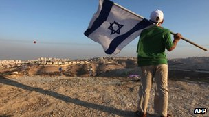 Israeli boy holds his national flag during a protest near the Jewish settlement of Maale Adumim, east of Jerusalem, in 2009