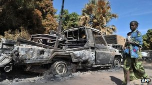 A girl walks past vehicle destroyed during an aerial bombing by France in Diabaly, Mali, on 21 January 2013