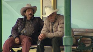 Two men sit on a bench in Laredo, Texas