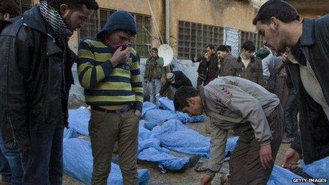 Men look for their relatives amongst the bodies of Syrian civilians executed and dumped in the Quweiq river