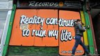 Bordered up record shop reads &quot;reality continues to ruin my life&quot; 