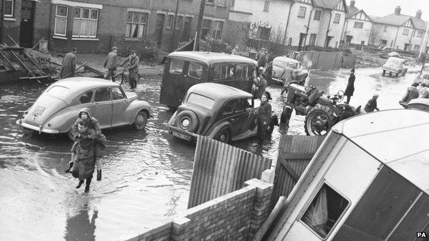 A woman is carried along a flooded street in the Wansbeck road area in King&#039;s Lynn in 1953