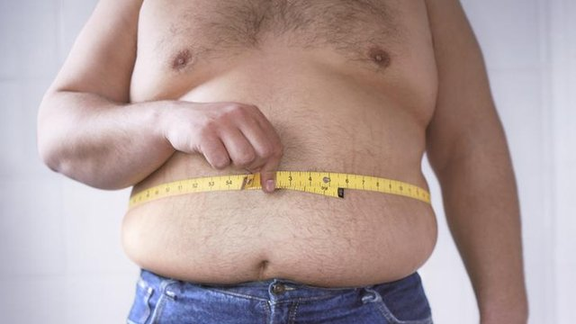 A man measuring his waist
