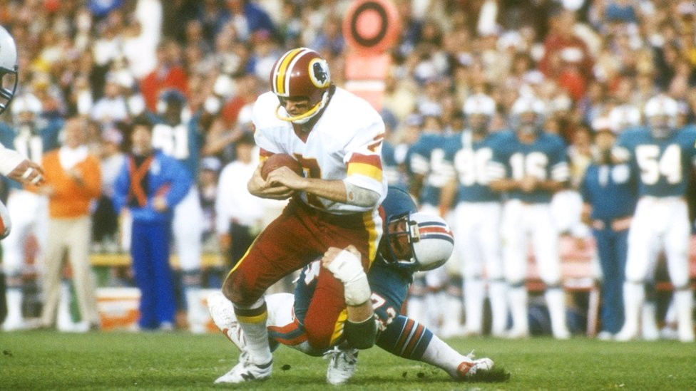 Quarterback Joe Theismann of the Washington Redskins gets tackled by a Miami Dolphins defensive player