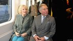 The Duchess of Cornwall and the Prince of Wales sit on a train