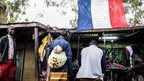 A French flag and tailors in the main market of Mopti, Mali