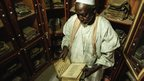 The imam of the great mosque in Djenne looking at ancient manuscripts