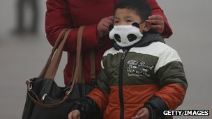 A boy wears a mask on Beijing's Tiananmen Square