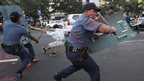 Anti-riot policemen, splattered with paint from protesters, use batons as they disperse a demonstration calling for a pullout of US troops and against the grounded USS Guardian minesweeper - January 25