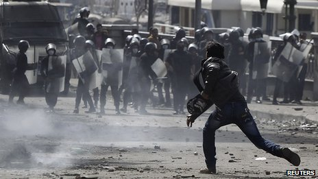A protester opposing Egyptian President Mohamed Mursi throws stone at riot police during clashes in Cairo
