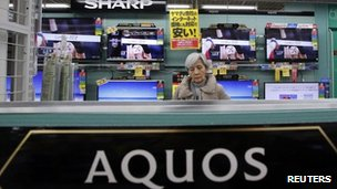 A woman looks around Sharp's TV sets at an electronic shop in Tokyo