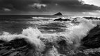 A black and white photo of the sea battering a rocky shoreline. Dark clouds loom over the horizon.