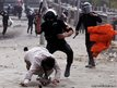 Riot policemen beat a protester opposing Egyptian President Mohamed Mursi, during clashes along Qasr Al Nil bridge, Cairo