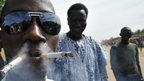 A man in Ansongo in Mali smoking two cigarettes - Tuesday 29 January 2013